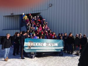 """Students and people in the commnity gather at SHS school with the """"Choose Respect"""" banner."""