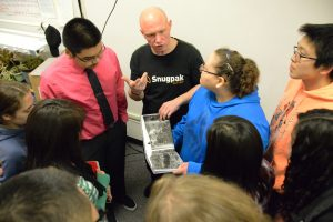Ed Gold shows his book about Wales, Alaska, with the students in the journalism class.