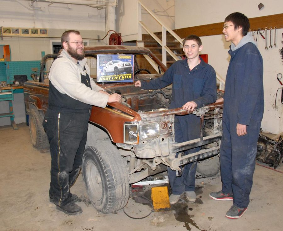 Automotive+teacher+Josh+Pittsenbarger+%28left%29+guides+students+Zelek+McNeilley+%28in+vehicle%29+and+Lynn-Victor+Lonewolf+working+on+the+flood-damaged+truck.