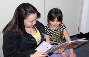 GILA sophomore Regina Harry reads a book to Galena elementary student Lily Esmailka.