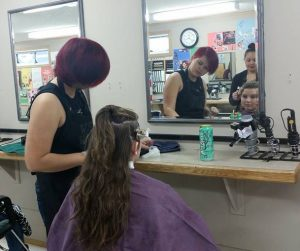 Senior Stormi Hocutt looks at her new hair style from budding cosmetologist Bobby Sheldon and teacher Liza Ashley.
