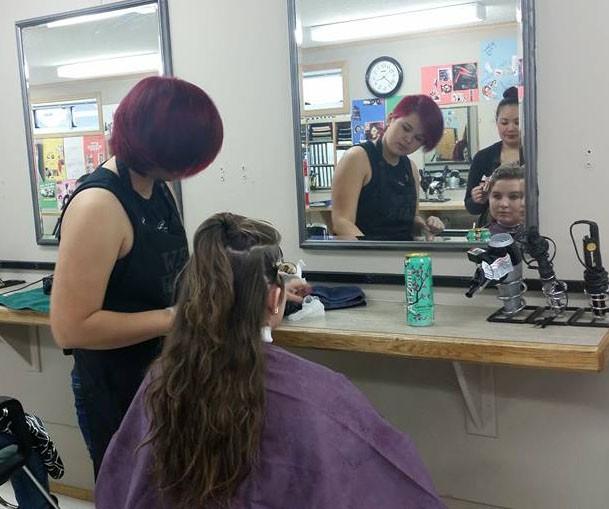 Senior+Stormi+Hocutt+looks+at+her+new+hair+style+from+budding+cosmetologist+Bobby+Sheldon+and+teacher+Liza+Ashley.