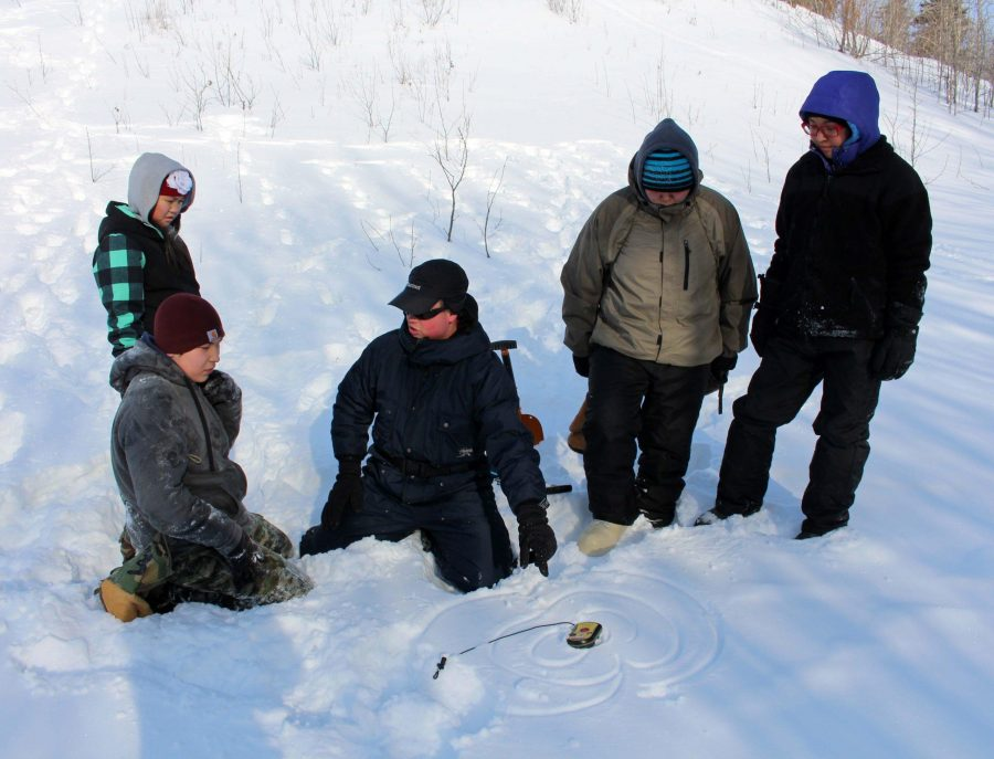 Sean DeWalt, a risk management specialist working along with teacher Tim Kalke, shows students how to use an avalanche beacon. Photo by Sarah Brown.