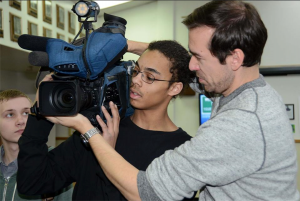 KTUU Dan Carpenter shows aspiring videographer how to operate the kind of camera used to record the evening news.