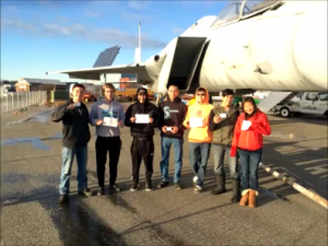 Aviation students in Anchorage standing in front of an F-15 fighter jet at the Alaska Aviation Heritage Museum holding their third class medical certificates.