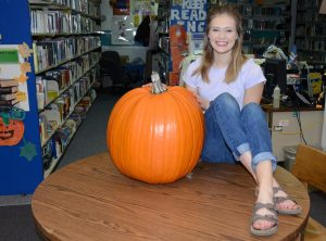 Sarah Brown gets the prize with her 60-pound pumpkin for the cross-country fundraiser, and the community will be served with lots of pies and other goodies as she shares her good fortune.